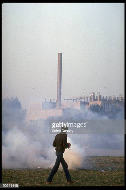 Lone protestor standing amidst tear gascoverd lawn during anitnuclear demontration in front of Honnepel reactor building