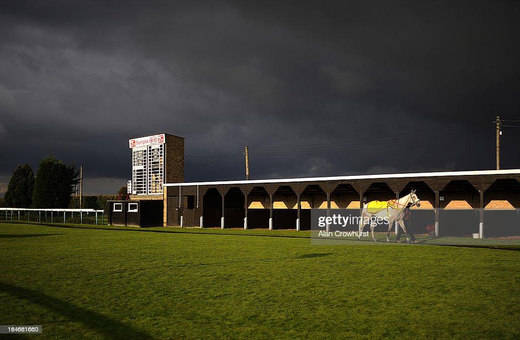 A lone runner walks in the parade ring as dark skies loom at Huntingdon racecourse on October 15 2013 in Huntingdon England