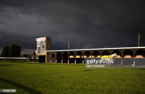 A lone runner walks in the parade ring as dark skies loom at Huntingdon racecourse on October 15 2013 in Huntingdon England