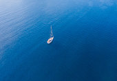 A lone sailing boat at anchor. The view from the air. Drone photo.