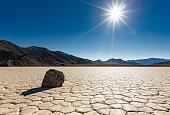 A lone 'sailing rock' sits basking in the bright unrelenting sun at Racetrack Playa in Death Valley National Park, California