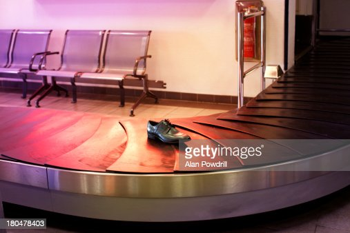 Lone shoe on airport baggage carousel