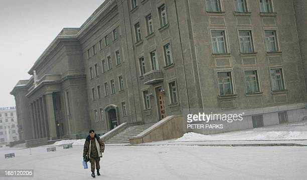 A lone soldier leaves Mongolia's parliament building after the coalition government collapsed after parliament voted to accept a mass resignation...