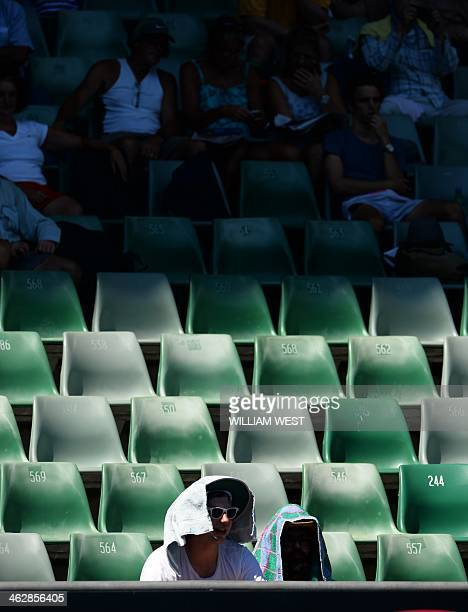 A lone spectator braves the blazing sun while others sit in the shade as they watch Alize Cornet of France play against Camila Giorgi of Italy during...