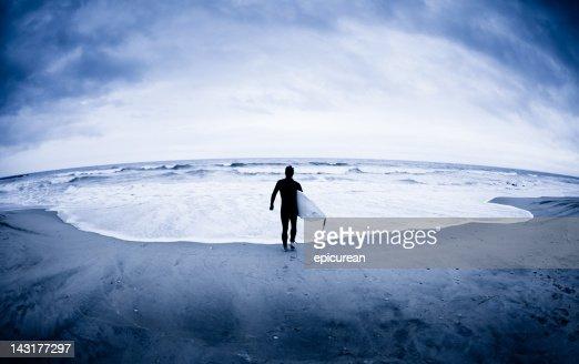 Lone surfer at edge of Atlantic Ocean in winter