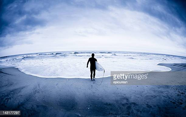 Lone surfer at edge of Atlantic Ocean in winter