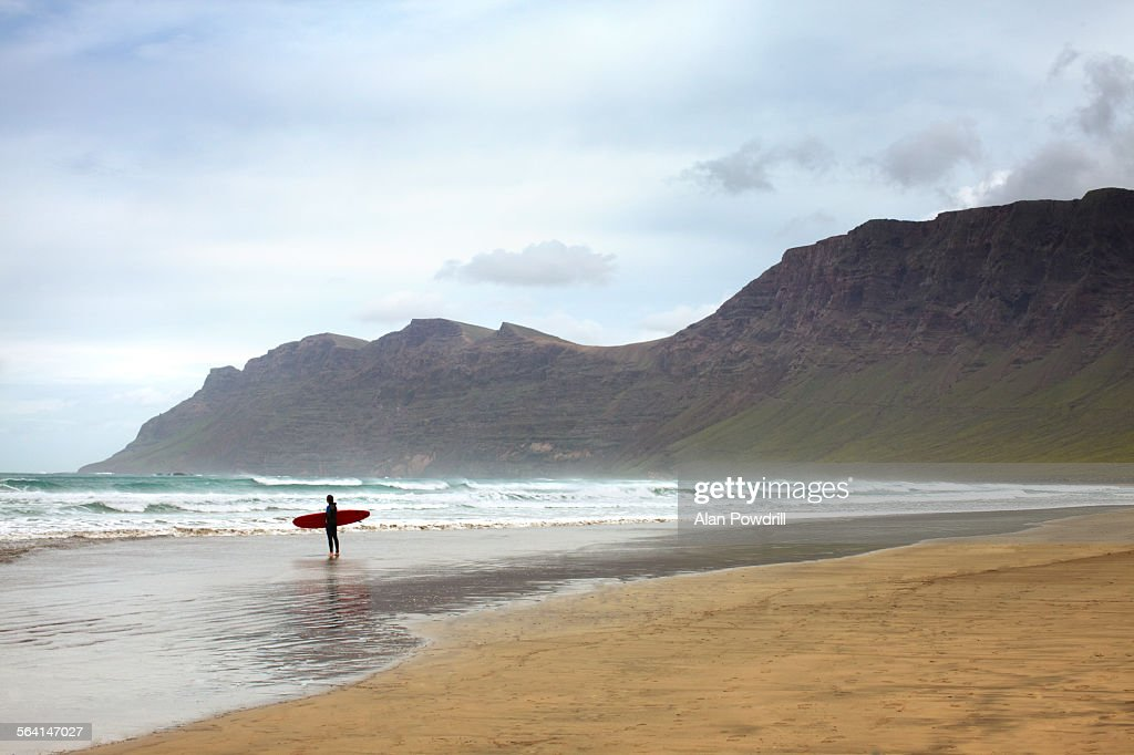 Lone surfer looking out to sea