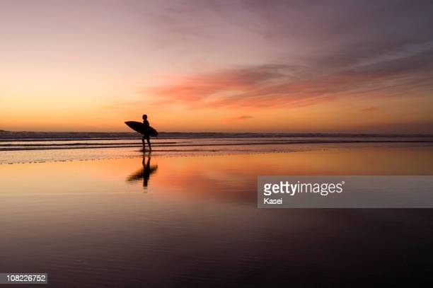 Lone surfer on beach at sunset