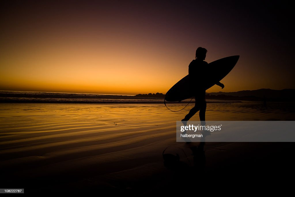 Lone surfer on the beach : Stock Photo