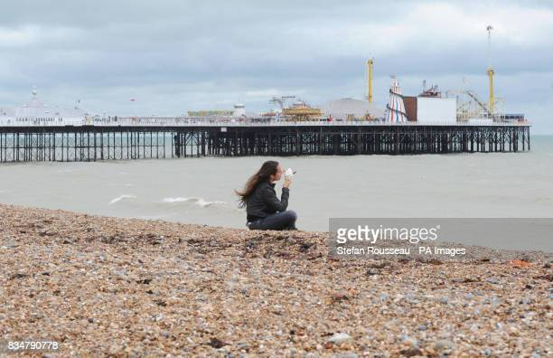 A lone visitor to Brighton beach today enjoys an ice cream despite the wet weather
