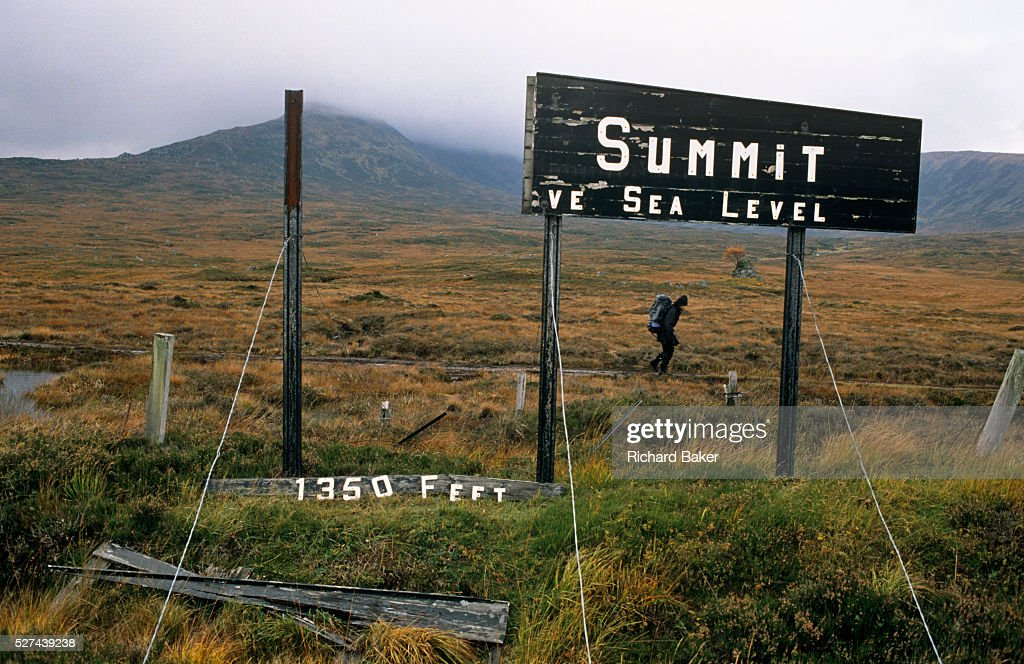 A lone walker passes by a partiallycollapsed broken sign announcing the summit of Rannoch Moor Scotland UK350 feet above sea level He is hunched...