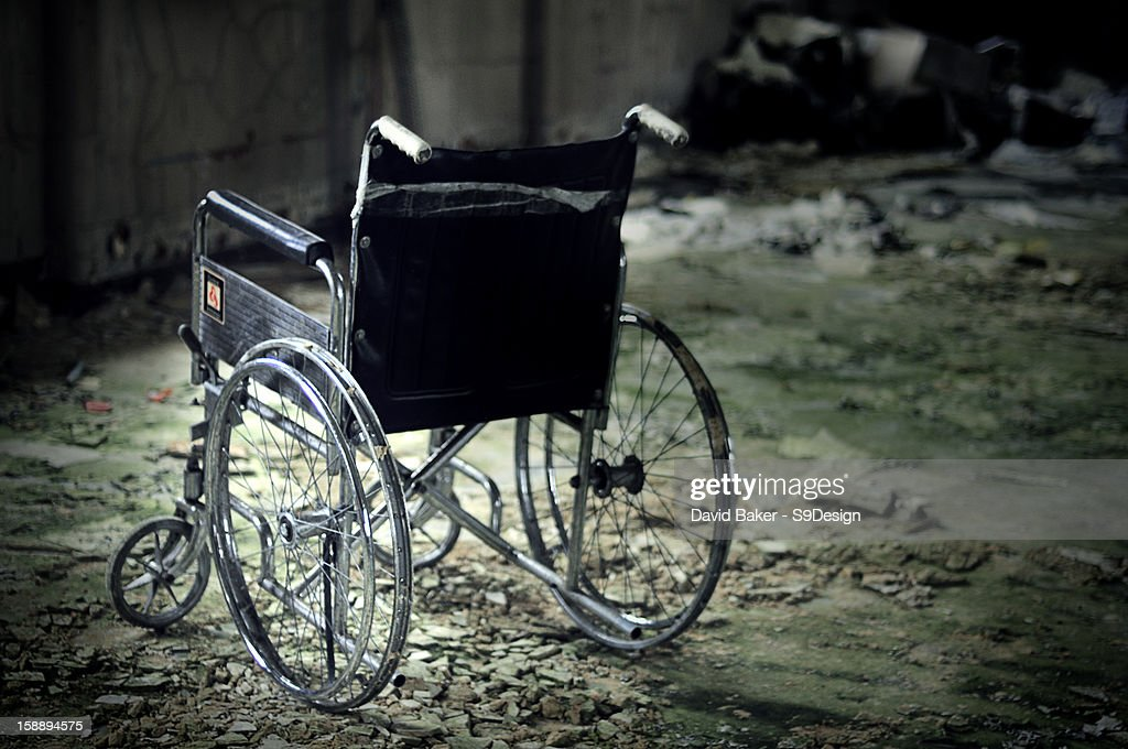 Lone Wheelchair in abandoned mental asylum : Stock Photo
