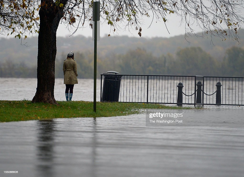 A lone woman stands in Waterfront Park looking out over the swollen Potomac River during high tide behind her is a lightly flooded Prince Street All...