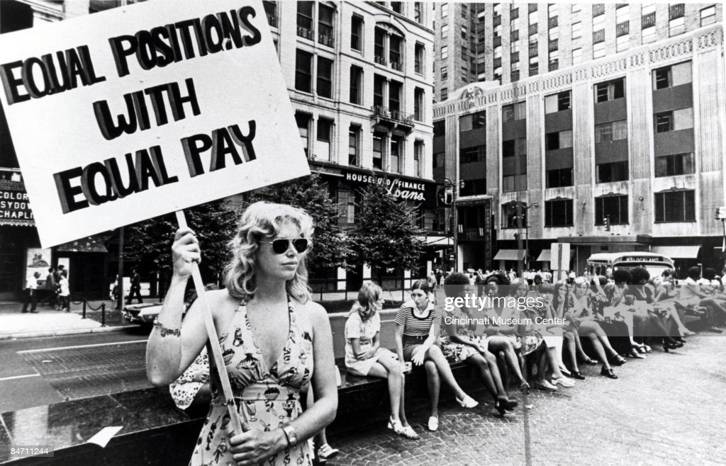A lone woman stands on a corner protesting unequal pay for women in an unidentified section of Cincinnati, Ohio, ca.1970s.
