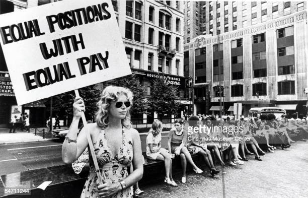 A lone woman stands on a corner protesting unequal pay for women in an unidentified section of Cincinnati Ohio ca1970s