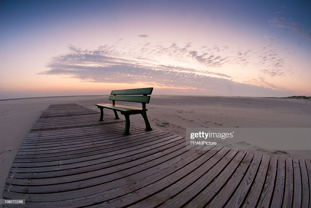 Lonely beach with a bench : Stock Photo