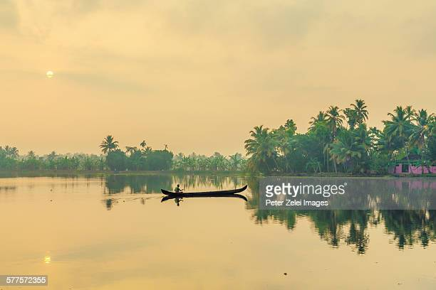 Lonely boatman in the tropical sunrise