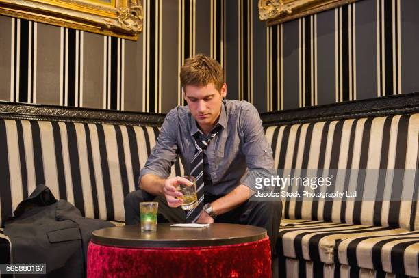 Lonely Caucasian businessman drinking in lounge