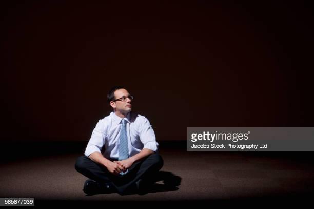 Lonely Caucasian businessman sitting on floor in spotlight