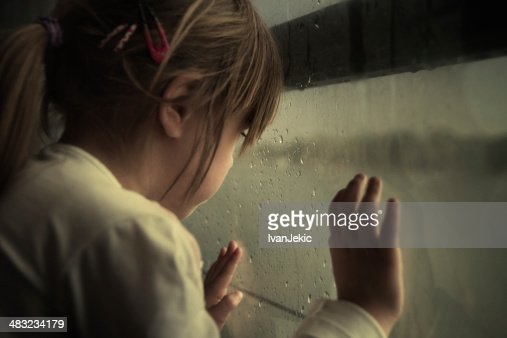 Lonely child looking through window
