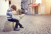 Upset problem child sitting on a street corner concept for bullying, depression, child protection or loneliness