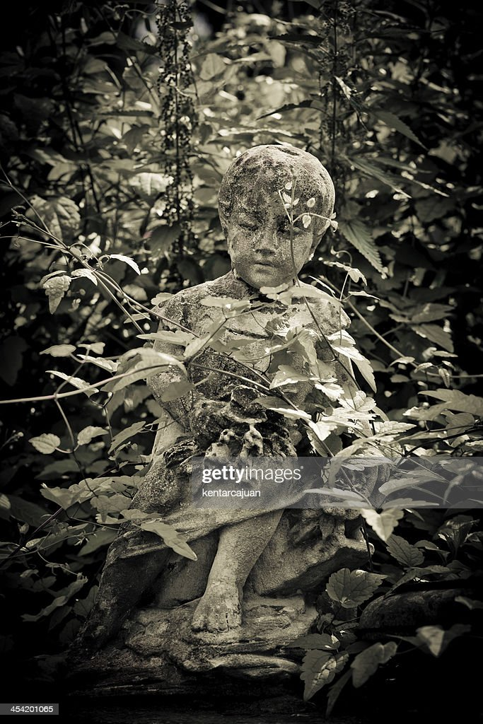 Lonely child tomb covered by shrubs : Stock Photo