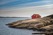 Red cottage on a remote location in the Swedish archipelago. Bohuslan, Sweden.