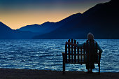 A lonely woman sitting by herself by a lake at sunset. Concept photo of loneliness, depression, divorce, or widowed. Looking toward a brighter future. Photographed at Lake Crescent, Olympic National P