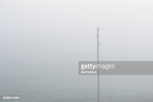 Lonely electricity cable line in strong fog : Stock Photo