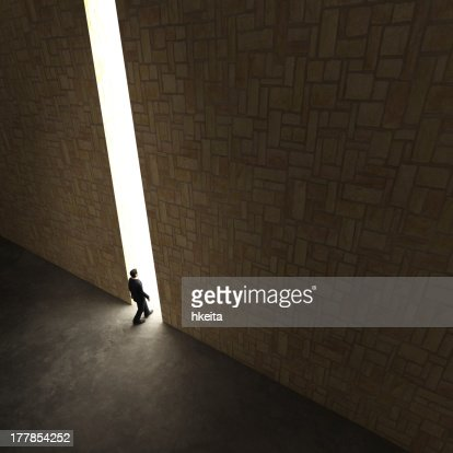 Lonely explorer walks through small gap in tall stone wall : Stock Photo