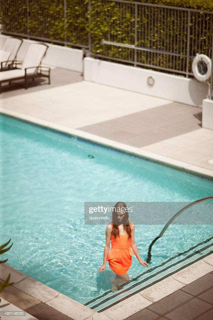 lonely girl in dress standing inside swimming pool stock photo - Inside Swimming Pool