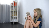 Lonely girl playing with favorite teddy bear toy, child custody, kindergarten