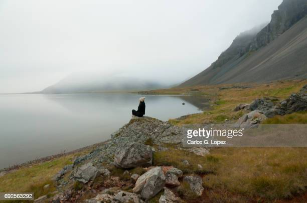 Lonely girl sits on rock near misty lake