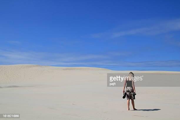 Lonely girl walking in sand dunes / desert