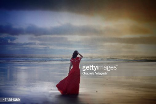 Lonely girl with red vintage dress at the beach