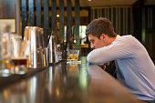 Lonely Hispanic businessman sitting at bar