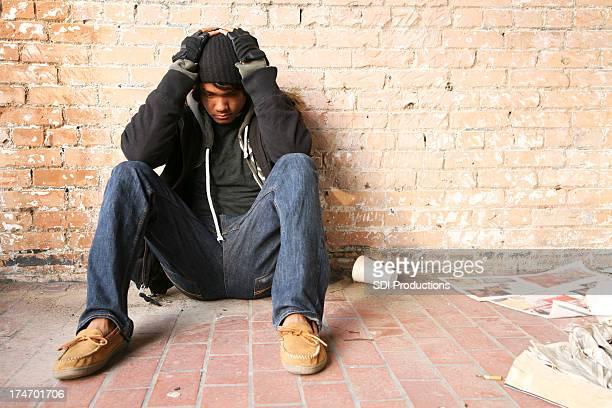 Lonely たこのホームレスの男性は、手で彼の頭