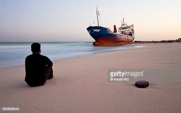 Lonely man sitting infront of grounded ship