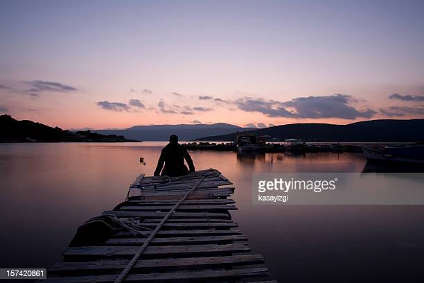 lonely man sitting side of the dock