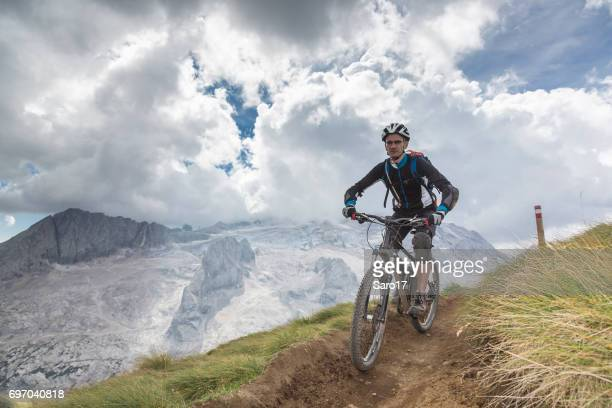 Lonely mountainbiker is riding a narrow single trail in front of Mt. Marmolada, Dolomites, Italy