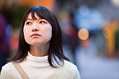 Outdoor portrait of a sad but beautiful looking young Asian woman