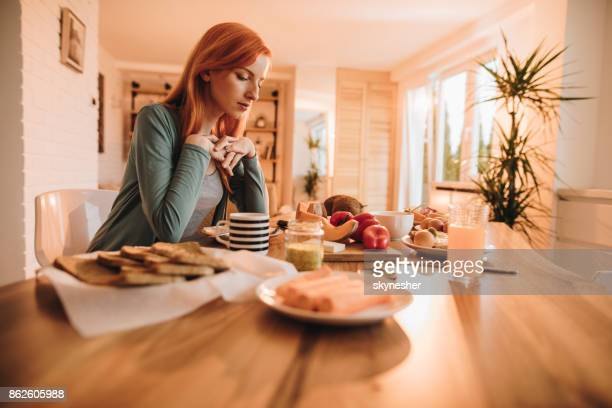 Lonely redhead woman thinking about something while having a meal at home.