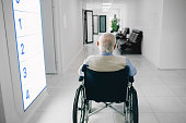 Lonely senior man in wheelchair sitting at the hospital corridor, back view.