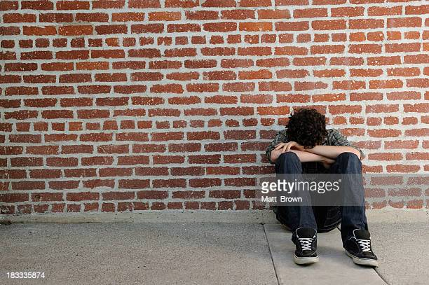 Lonely teenager sits against brick wall with arms cover eyes