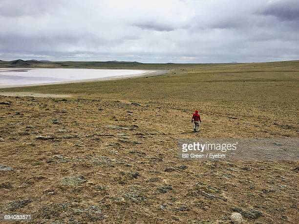 Lonely Tourist Walking On Arid Landscape