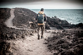 lonely traveler man young middle age with trekking clothes and backpack walking on the ocean coastline in a rocks desert. following a path with sea view and enjoying freedom and alternative lifestyle