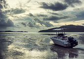 Lonely white motor boat aground in Andaman sea on sunrise. Beautiful dramatic landscape in background. Loneliness, faylure concept. Text space