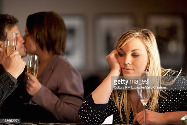 Lonely woman at bar with kissing couple