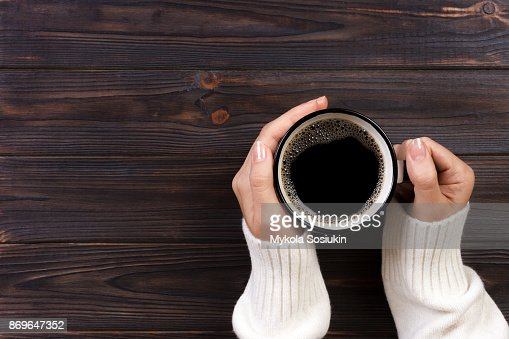 Lonely woman drinking coffee in the morning, top view of female hands holding cup of hot beverage on wooden desk : Stock Photo