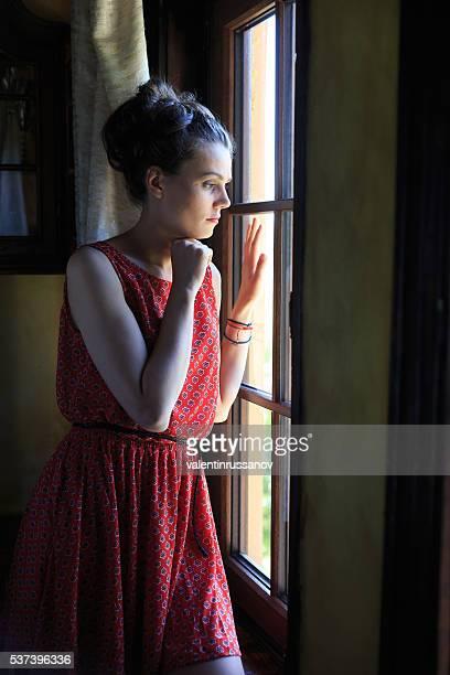 Solitaire femme regardant par la fenêtre